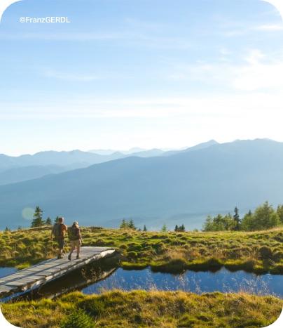 Wanderer überqueren einen Natursee in den Bergen