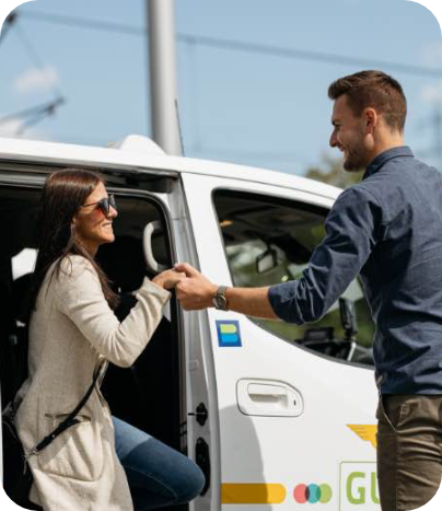 Frau steigt mit Hilfe eines Mannes aus dem ISTmobil Taxi